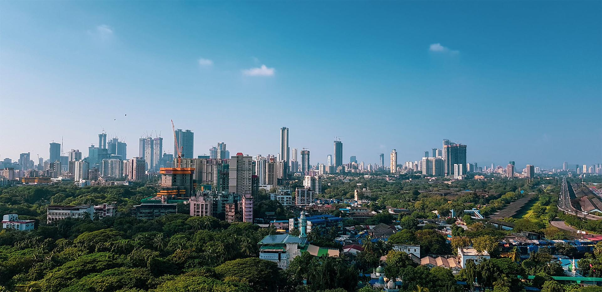 Mumbai's skyline against clear blue skies with cranes dotting the landscape, showcasing infrastructure development.